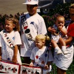 SarahBee on right holding baby cousin, her sister E with the sweet blond pigtails, and sister A in the French Braids with the America sash. Our cousin J stands tall with his Freedom sash
